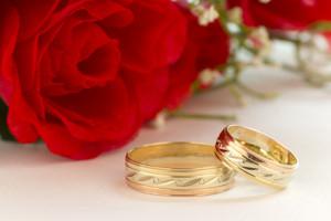 Hochzeitstringe zusammen mit einer roten Rose